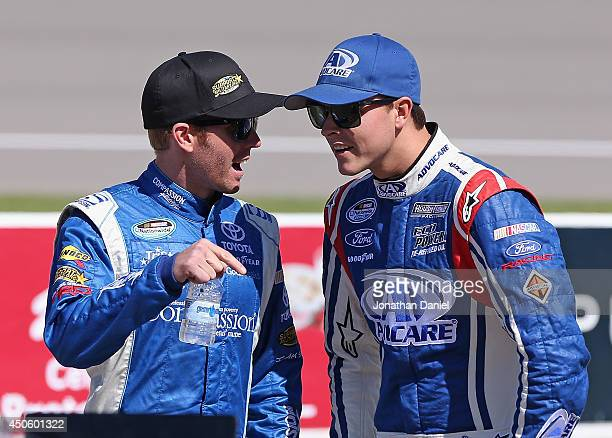 Blake Koch driver of the CompassionRacingcom Toyota left talks with Trevor Bayne driver of the AdvoCare Ford on the grid during qualifying for the...