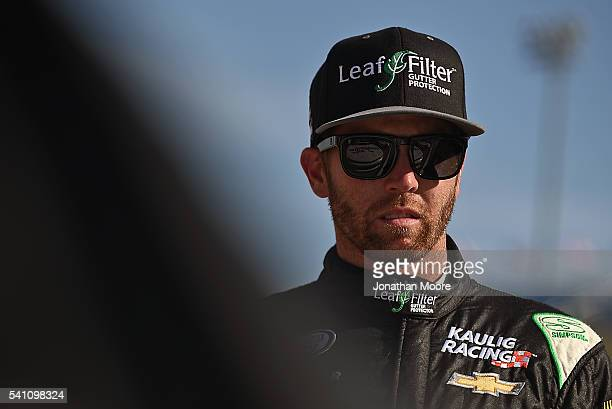 Blake Koch driver of the Leaf Filter Gutter Protection Chevrolet stands next to his car during qualifying for the NASCAR Camping World Truck Series...