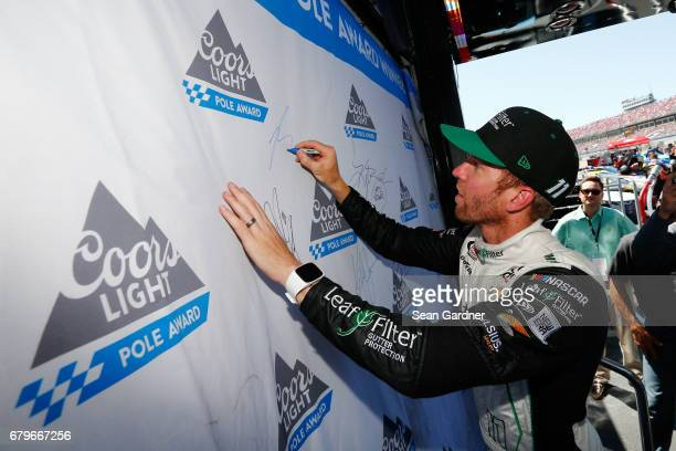 Blake Koch driver of the LeafFilter Gutter Protection Chevrolet signs the Coors Light Pole board after qualifying for the pole position for the...