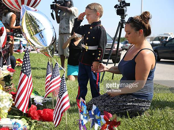 Blake Miller and his mother Ashley Miller whose husband is a Lieutenant in the Marine Corps pay their respects to those killed while visiting a...