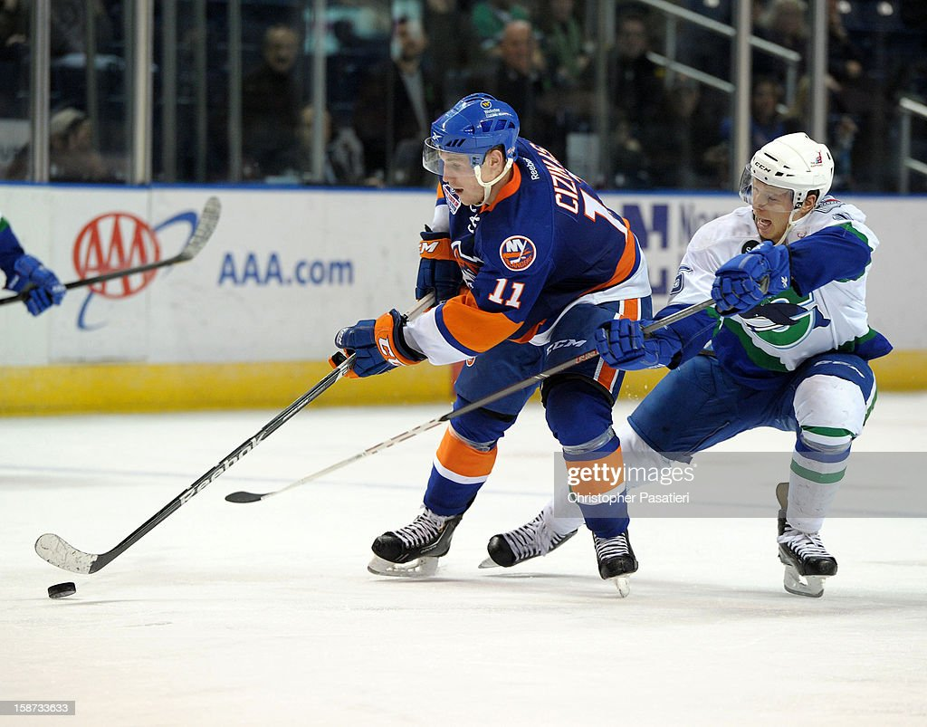 Blake Parlett #5 of the Connecticut Whale and Casey Cizikas #11 of the Bridgeport Sound Tigers chase after the puck during an American Hockey League game on December 26, 2012 at the Webster Bank Arena at Harbor Yard in Bridgeport, Connecticut.