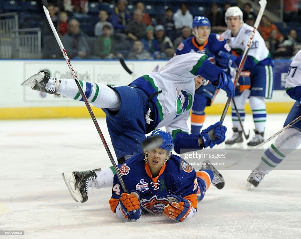 Blake Parlett #5 of the Connecticut Whale falls over David Ullstrom #24 of the Bridgeport Sound Tigers after checking him during an American Hockey League game on December 26, 2012 at the Webster Bank Arena at Harbor Yard in Bridgeport, Connecticut.