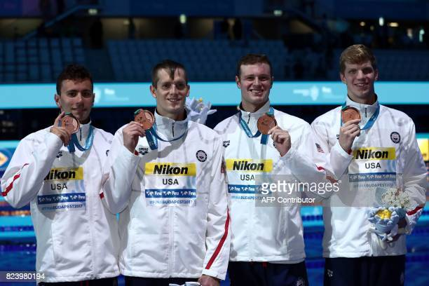 US Blake Pieroni US Townley Haas US Jack Conger and US Zane Grothe celebrate on the podium after the men's 4x200m freestyle relay final during the...