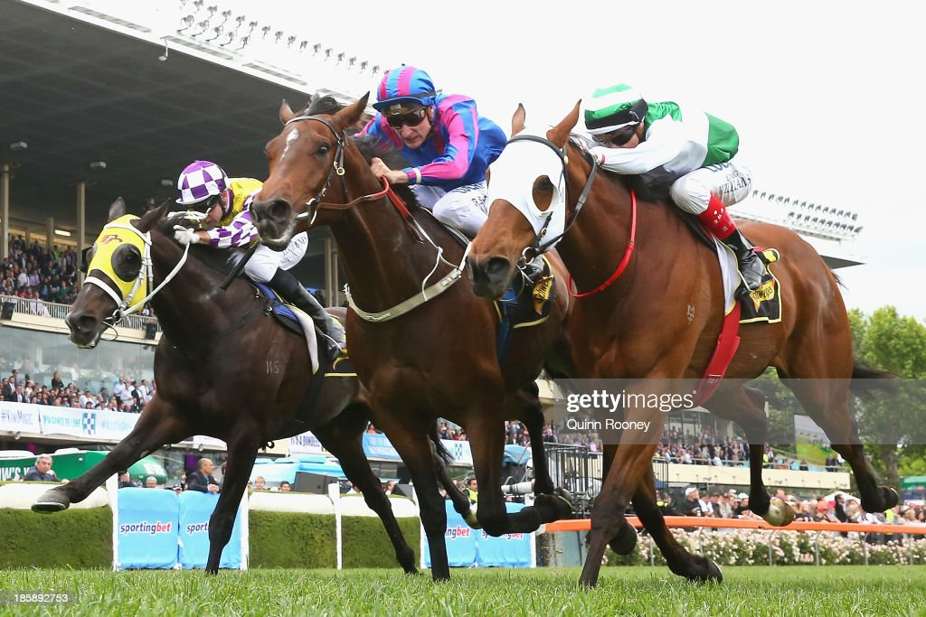 Blake Shinn riding Toydini (c) crosses the line to win the Schweppes Crystal Mile just infront of Craig Williams riding Speediness (r) during Cox Plate Day at Moonee Valley Racecourse on October 26, 2013 in Melbourne, Australia.