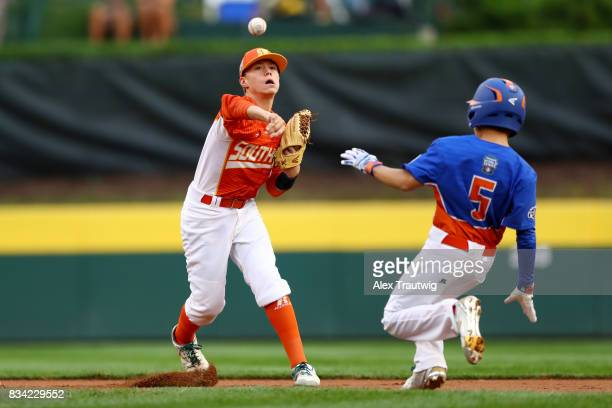Blake Slaga of the Southwest team from Texas throws to first as Matthew Greene of the Great Lakes team from Michigan slides into second base during...