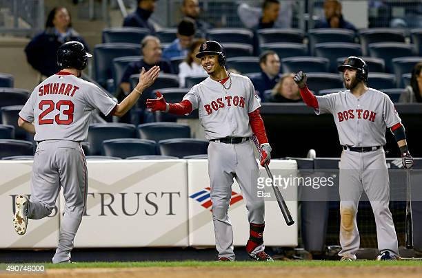 Blake Swihart of the Boston Red Sox is congratulated by teammates Mookie Betts and Dustin Pedroia after Swihart scored in the 11th inning against the...