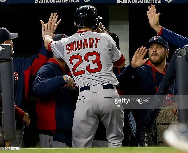 Blake Swihart of the Boston Red Sox is congratulated by Wade Miley in the dugout after he scored on a sacrifice bunt in the 11th inning against the...
