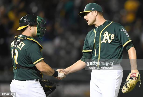 Blake Treinen and Josh Phegley of the Oakland Athletics shake hands after they defeated the Texas Rangers 41 at Oakland Alameda Coliseum on September...