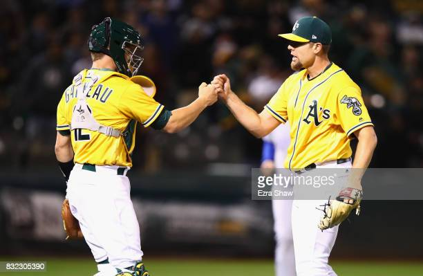 Blake Treinen high fives with Dustin Garneau of the Oakland Athletics reacts after they beat the Kansas City Royals at Oakland Alameda Coliseum on...