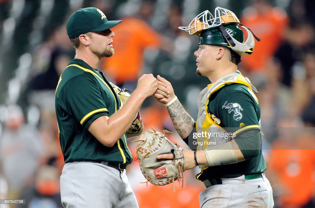 Blake Treinen #39 of the Oakland Athletics celebrates with Bruce Maxwell #13 after a 6-4 victory against the Baltimore Orioles at Oriole Park at Camden Yards on August 22, 2017 in Baltimore, Maryland.
