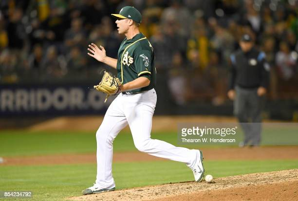 Blake Treinen of the Oakland Athletics reacts as he can't find the ball that hit him off the bat of Brett Nicholas of the Texas Rangers in the top of...