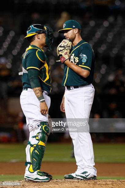 Blake Treinen of the Oakland Athletics talks to Bruce Maxwell during the eighth inning against the Tampa Bay Rays at the Oakland Coliseum on July 17...