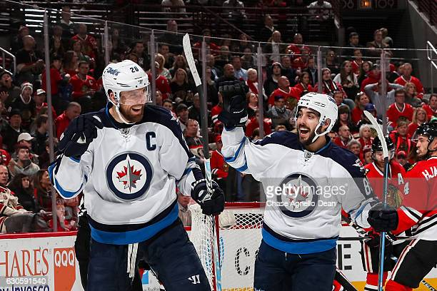Blake Wheeler and Mathieu Perreault of the Winnipeg Jets celebrate after Wheeler scored against the Chicago Blackhawks in the first period at the...