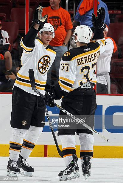 Blake Wheeler and Patrice Bergeron of the Boston Bruins celebrate after defeating the Philadelphia Flyers in Game Three of the Eastern Conference...