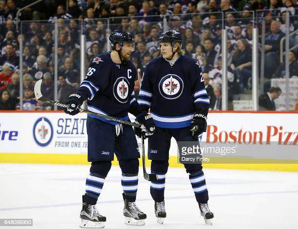Blake Wheeler and Patrik Laine off the Winnipeg Jets discuss strategy during a first period stoppage in play against the Colorado Avalanche at the...