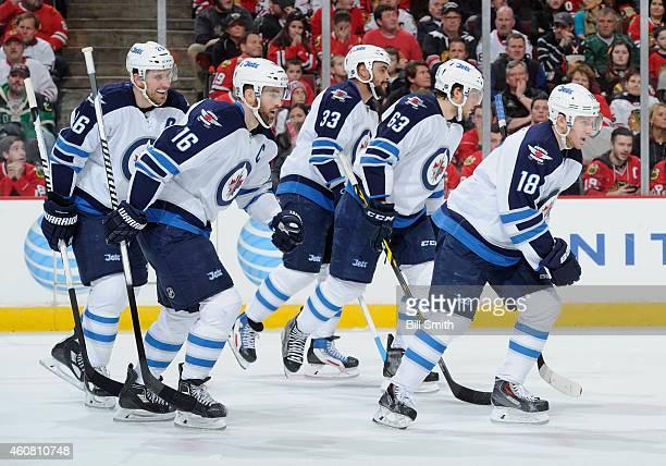 Blake Wheeler Andrew Ladd Dustin Byfuglien Ben Chiarot and Bryan Little of the Winnipeg Jets skate toward the bench after Little scored against the...