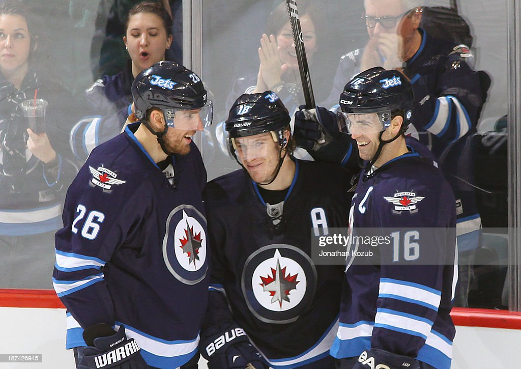 <a gi-track='captionPersonalityLinkClicked' href=/galleries/search?phrase=Blake+Wheeler&family=editorial&specificpeople=716703 ng-click='$event.stopPropagation()'>Blake Wheeler</a> #26, <a gi-track='captionPersonalityLinkClicked' href=/galleries/search?phrase=Bryan+Little&family=editorial&specificpeople=540533 ng-click='$event.stopPropagation()'>Bryan Little</a> #18 and <a gi-track='captionPersonalityLinkClicked' href=/galleries/search?phrase=Andrew+Ladd&family=editorial&specificpeople=228452 ng-click='$event.stopPropagation()'>Andrew Ladd</a> #16 of the Winnipeg Jets share a smile after Little scored his second goal of the game against the Nashville Predators during third period action at the MTS Centre on November 8, 2013 in Winnipeg, Manitoba, Canada.