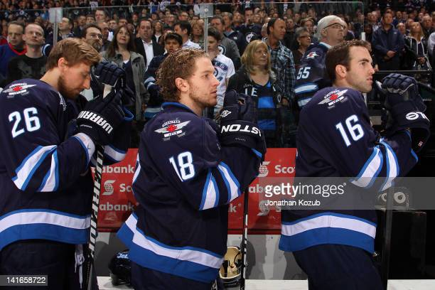 Blake Wheeler Bryan Little and Andrew Ladd of the Winnipeg Jets stand on the bench during the singing of the National anthems prior to NHL action...