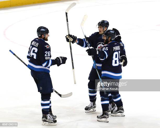 Blake Wheeler Mark Scheifele and Mathieu Perreault of the Winnipeg Jets celebrate a second period goal against the Vancouver Canucks at the MTS...