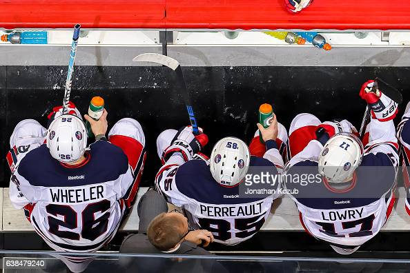 Blake Wheeler Mathieu Perreault and Adam Lowry of the Winnipeg Jets look on from the bench during second period action against the Calgary Flames at...