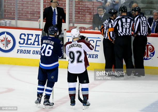 Blake Wheeler of the Winnipeg Jets and Gabriel Landeskog of the Colorado Avalanche wait as the officials confer over a call during second period...