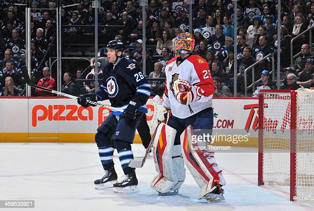 Blake Wheeler of the Winnipeg Jets and goaltender Jacob Markstrom of the Florida Panthers keep an eye on the play during first period action at the...