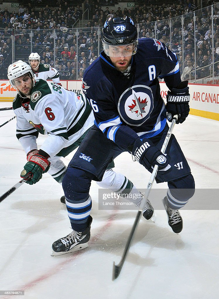 Blake Wheeler #26 of the Winnipeg Jets and Marco Scandella #6 of the Minnesota Wild keep an eye on the play along the boards during first period action at the MTS Centre on April 7, 2014 in Winnipeg, Manitoba, Canada.