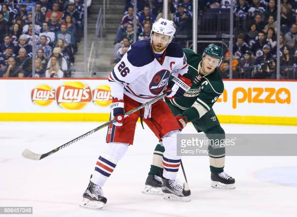 Blake Wheeler of the Winnipeg Jets and Mikko Koivu of the Minnesota Wild keep an eye on the play during first period action at the MTS Centre on...