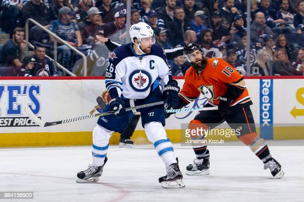 Blake Wheeler of the Winnipeg Jets and Patrick Eaves of the Anaheim Ducks keep an eye on the play during first period action at the MTS Centre on...