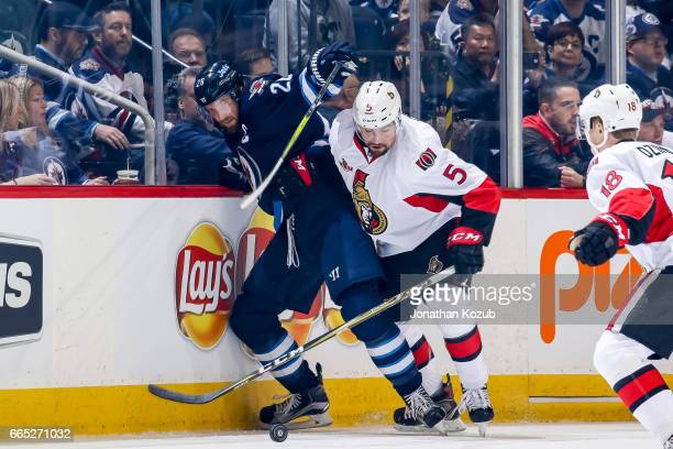 Blake Wheeler of the Winnipeg Jets battles Cody Ceci of the Ottawa Senators along the boards during first period action at the MTS Centre on April 1...