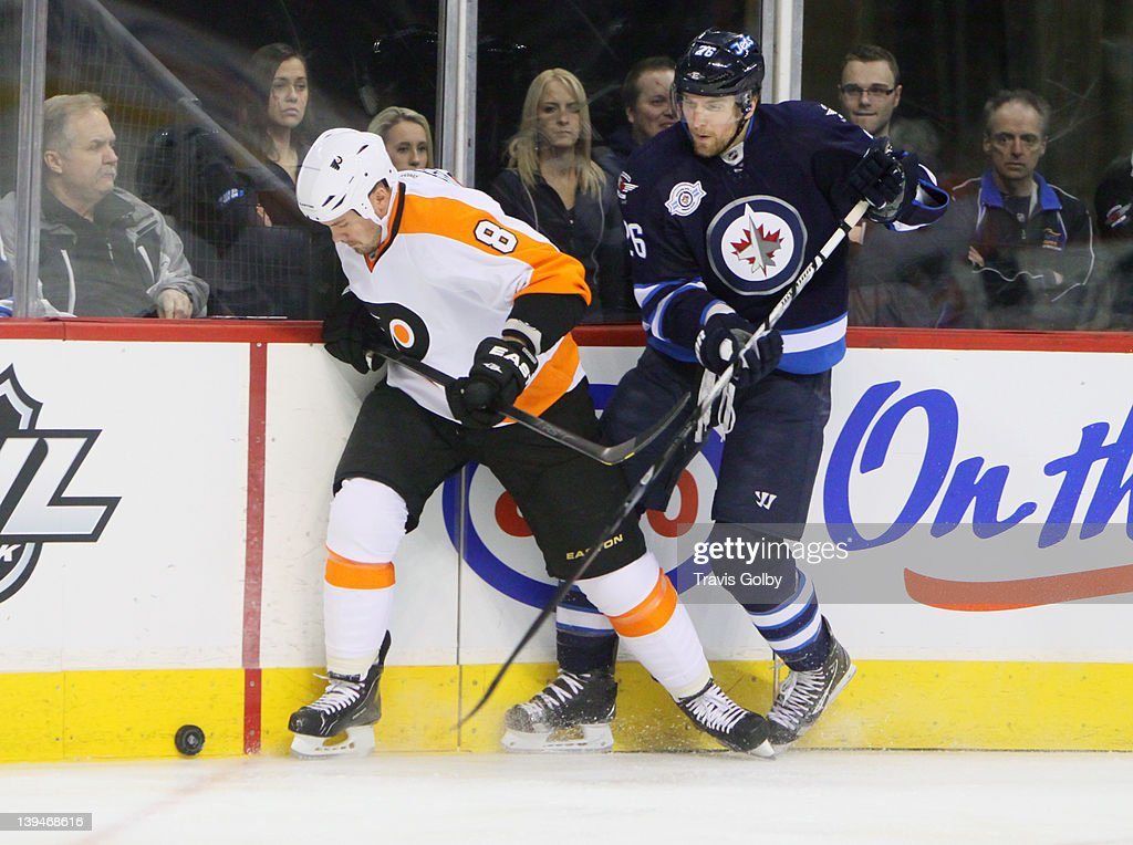 Blake Wheeler #26 of the Winnipeg Jets battles Nicklas Grossman #8 of the Philadelphia Flyers along the boards for possession of the puck during first period action at the MTS Centre on February 21, 2012 in Winnipeg, Manitoba, Canada.