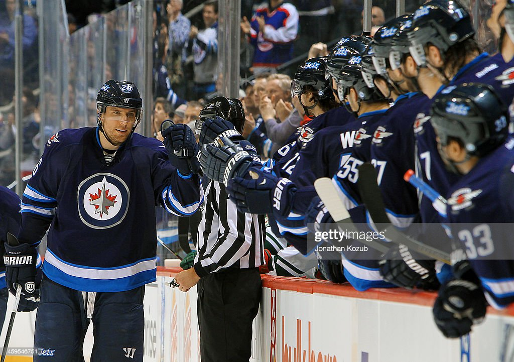 <a gi-track='captionPersonalityLinkClicked' href=/galleries/search?phrase=Blake+Wheeler&family=editorial&specificpeople=716703 ng-click='$event.stopPropagation()'>Blake Wheeler</a> #26 of the Winnipeg Jets celebrates a first period goal against the Minnesota Wild with teammates at the bench at the MTS Centre on December 27, 2013 in Winnipeg, Manitoba, Canada.