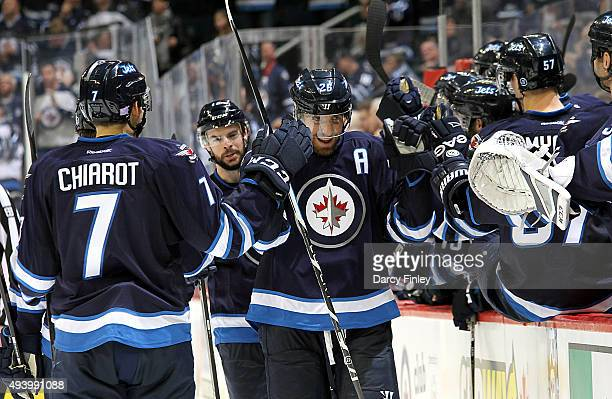 Blake Wheeler of the Winnipeg Jets celebrates a third period goal against the Tampa Bay Lightning with teammates at the bench at the MTS Centre on...