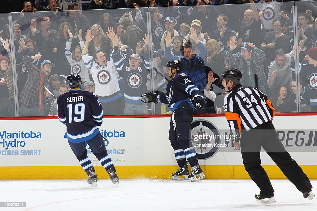 Blake Wheeler #26 of the Winnipeg Jets celebrates an empty net goal against the Pittsburgh Penguins with teammate Jim Slater #19 in front of enthusiastic fans at the MTS Centre on January 25, 2013 in Winnipeg, Manitoba, Canada. The Jets defeated the Pens 4-2.