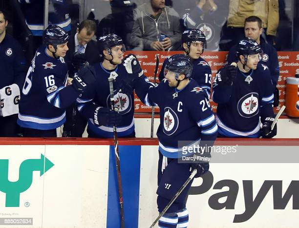 Blake Wheeler of the Winnipeg Jets celebrates his second period goal against the Ottawa Senators with teammates at the bench at the Bell MTS Place on...