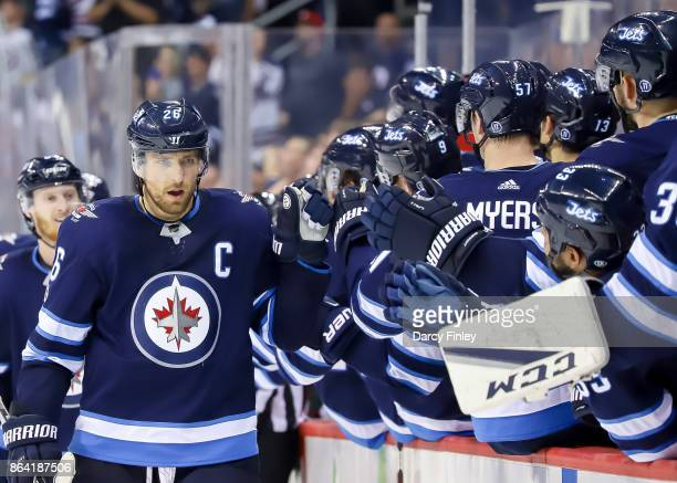 Blake Wheeler of the Winnipeg Jets celebrates his third period goal against the Minnesota Wild with teammates at the bench at the Bell MTS Place on...