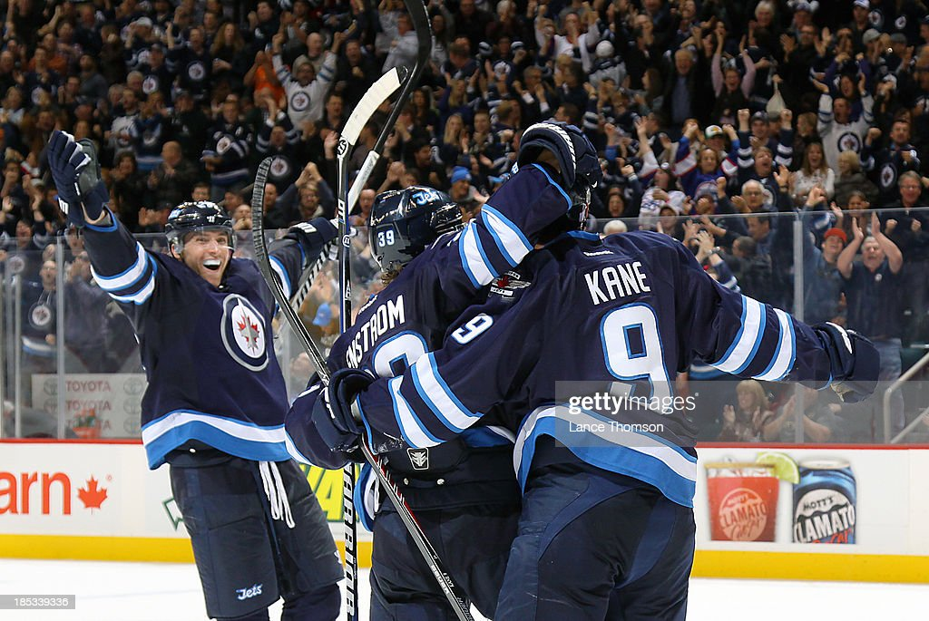 <a gi-track='captionPersonalityLinkClicked' href=/galleries/search?phrase=Blake+Wheeler&family=editorial&specificpeople=716703 ng-click='$event.stopPropagation()'>Blake Wheeler</a> #26 of the Winnipeg Jets celebrates with teammates <a gi-track='captionPersonalityLinkClicked' href=/galleries/search?phrase=Tobias+Enstrom&family=editorial&specificpeople=2538468 ng-click='$event.stopPropagation()'>Tobias Enstrom</a> #39 and <a gi-track='captionPersonalityLinkClicked' href=/galleries/search?phrase=Evander+Kane&family=editorial&specificpeople=4303789 ng-click='$event.stopPropagation()'>Evander Kane</a> #9 to celebrate a third-period goal that tied the game against the St. Louis Blues at the MTS Centre on October 18, 2013 in Winnipeg, Manitoba, Canada.