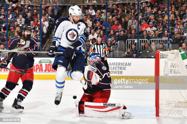 Blake Wheeler of the Winnipeg Jets collides with goaltender Joonas Korpisalo of the Columbus Blue Jackets while jumping to avoid the puck during the...