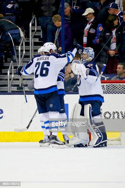Blake Wheeler of the Winnipeg Jets congratulates Eric Comrie of the Winnipeg Jets after defeating the Columbus Blue Jackets 54 on April 6 2017 at...