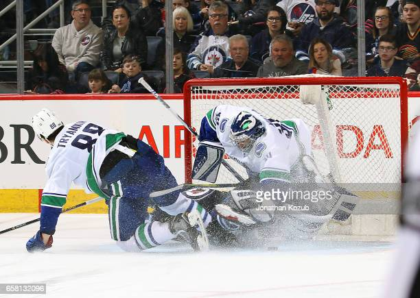Blake Wheeler of the Winnipeg Jets crashes into goaltender Ryan Miller of the Vancouver Canucks in the crease during third period action at the MTS...