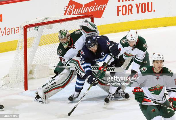 Blake Wheeler of the Winnipeg Jets fights his way between goaltender Darcy Kuemper and Marco Scandella of the Minnesota Wild as they keep an eye on...