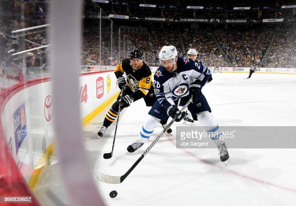 Blake Wheeler of the Winnipeg Jets handles the puck against Brian Dumoulin of the Pittsburgh Penguins at PPG Paints Arena on October 26 2017 in...
