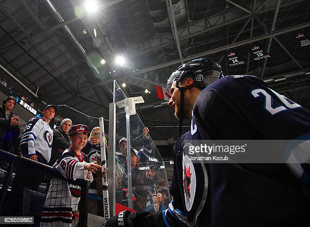 Blake Wheeler of the Winnipeg Jets hands a souvenir stick to a lucky fan after being named the first star of the game following a 32 victory over the...