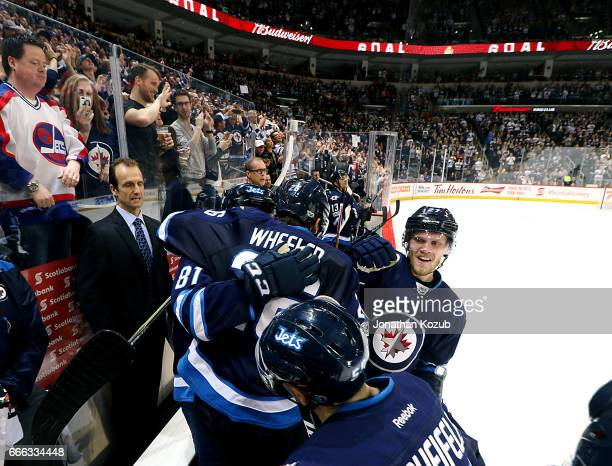 Blake Wheeler of the Winnipeg Jets hugs teammate Kyle Connor on the bench after scoring a third period shorthanded goal against the Nashville...