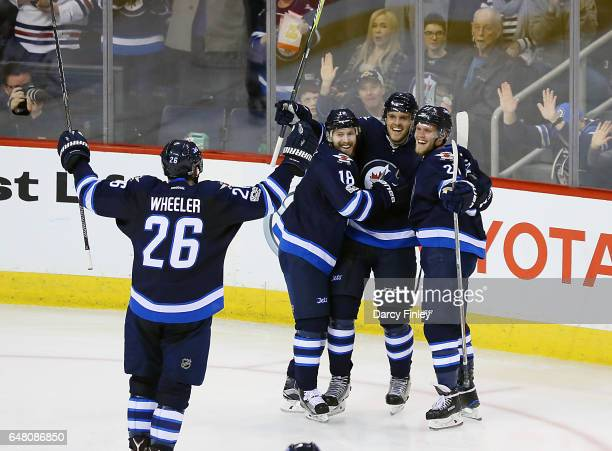 Blake Wheeler of the Winnipeg Jets joins teammates Bryan Little Ben Chiarot and Nikolaj Ehlers as they celebrate a second period goal against the...