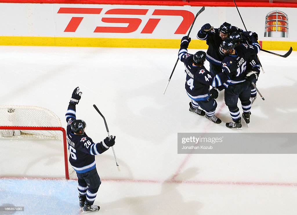<a gi-track='captionPersonalityLinkClicked' href=/galleries/search?phrase=Blake+Wheeler&family=editorial&specificpeople=716703 ng-click='$event.stopPropagation()'>Blake Wheeler</a> #26 of the Winnipeg Jets joins teammates <a gi-track='captionPersonalityLinkClicked' href=/galleries/search?phrase=Zach+Bogosian&family=editorial&specificpeople=4195061 ng-click='$event.stopPropagation()'>Zach Bogosian</a> #44, Grant Clitsome #24, <a gi-track='captionPersonalityLinkClicked' href=/galleries/search?phrase=Andrew+Ladd&family=editorial&specificpeople=228452 ng-click='$event.stopPropagation()'>Andrew Ladd</a> #16 and <a gi-track='captionPersonalityLinkClicked' href=/galleries/search?phrase=Bryan+Little&family=editorial&specificpeople=540533 ng-click='$event.stopPropagation()'>Bryan Little</a> #18 of the Winnipeg Jets as they celebrate a second period goal against the Florida Panthers at the MTS Centre on April 11, 2013 in Winnipeg, Manitoba, Canada.