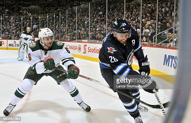 Blake Wheeler of the Winnipeg Jets plays the puck along the boards as Marco Scandella of the Minnesota Wild defends during first period action on...