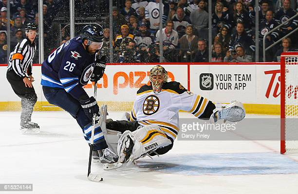 Blake Wheeler of the Winnipeg Jets plays the puck around a falling Tuukka Rask of the Boston Bruins for a first period goal at the MTS Centre on...