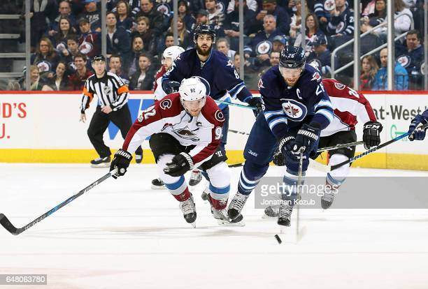 Blake Wheeler of the Winnipeg Jets plays the puck as Gabriel Landeskog of the Colorado Avalanche gives chase during first period action at the MTS...