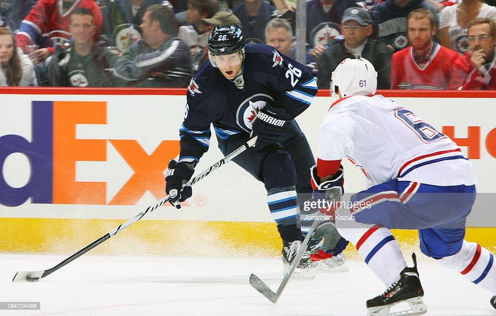 <a gi-track='captionPersonalityLinkClicked' href=/galleries/search?phrase=Blake+Wheeler&family=editorial&specificpeople=716703 ng-click='$event.stopPropagation()'>Blake Wheeler</a> #26 of the Winnipeg Jets plays the puck as <a gi-track='captionPersonalityLinkClicked' href=/galleries/search?phrase=Raphael+Diaz&family=editorial&specificpeople=5333791 ng-click='$event.stopPropagation()'>Raphael Diaz</a> #61 of the Montreal Canadiens defends during third period action at the MTS Centre on October 15, 2013 in Winnipeg, Manitoba, Canada.
